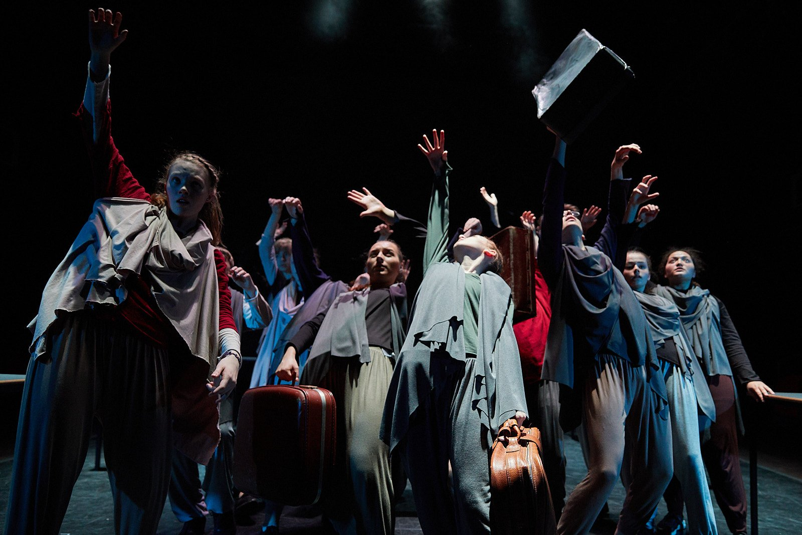 A group of young performers on stage. They are dressed in loose-fitting clothing that is blue, grey and red, and throwing their hands up into the air.
