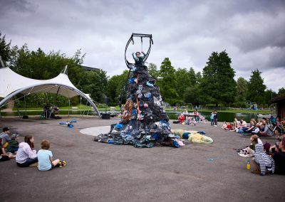 An outdoor performance. In the middle of a square, there is a tall aerial rig and a woman wearing a long dress made of rubbish and plastic bags.