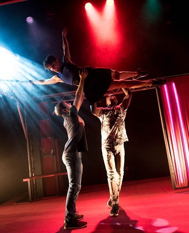 2 performers hold a third up in the air, on her side. They are on a stage, lit up by red and blue lights.
