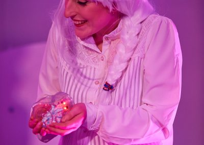 A woman in a long white wig holds a model heart in her cupped hands, smiling.