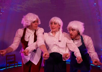 3 people in white wigs stand with their arms linked, looking at each other nervously.