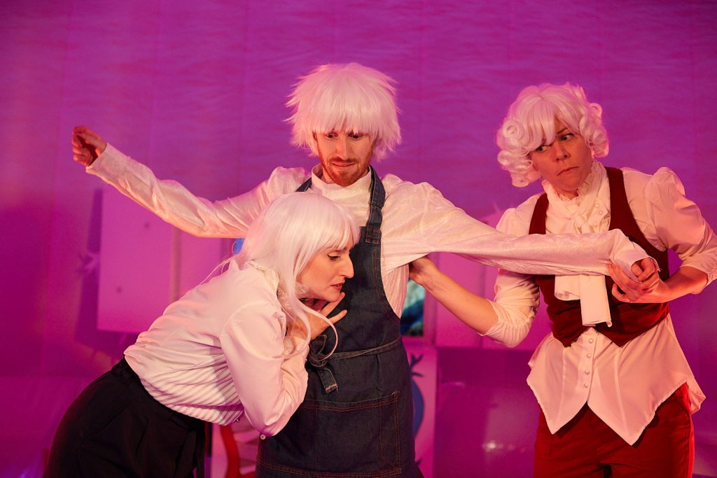 There are 2 women and a man against a pink background, wearing white wigs and colourful costumes. The man has his arms out to the sides and is looking shocked, while a woman listens to his heart, looking concerned.