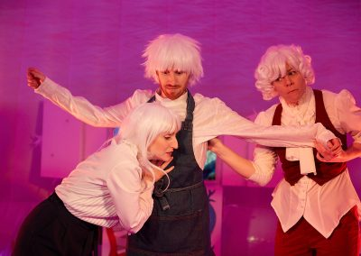 There are 2 women and a man against a pink background, wearing white wigs and colourful costumes. The man has his arms out to the sides and is looking shocked, while a woman listens to his heart.