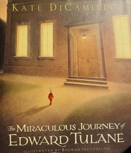 An illustration of a house. A small rabbit wearing a red jacket is approaching it. There is text saying 'The Miraculous Journey of Edward Tulane.'