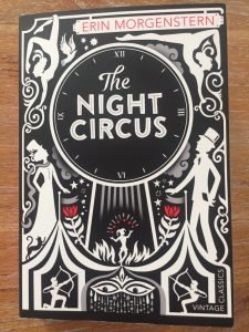 A black and white illustration of a circus. There is a title saying 'The Night Circus.'
