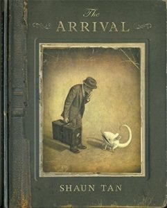 A green cover book with the title 'The Arrival.' There is a framed image of a person wearing a hat and holding a briefcase.