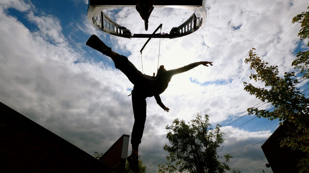 A silhouette of a woman flying in the air on a large aerial rig, against the clouds.
