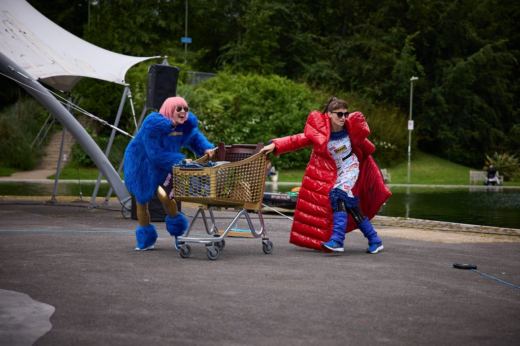 2 women in bright red and blue furry coats and sunglasses walk along confidently, pushing a shopping trolley.