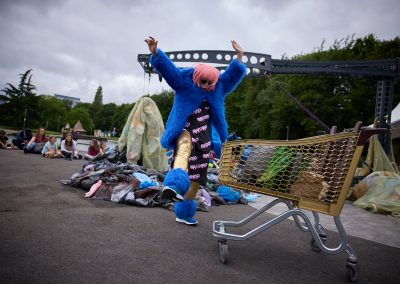 A woman in a pink wig, gold leggings and blue furry coat jumps in the air next to a shopping trolley.