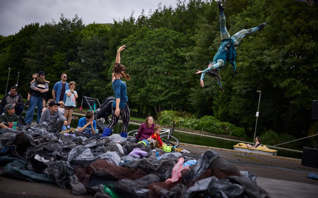 An outdoor performance, in the foreground with a big pile of rubbish. Behind it, a woman stands and reaches up in the air towards another performer who is suspended from an aerial rig.