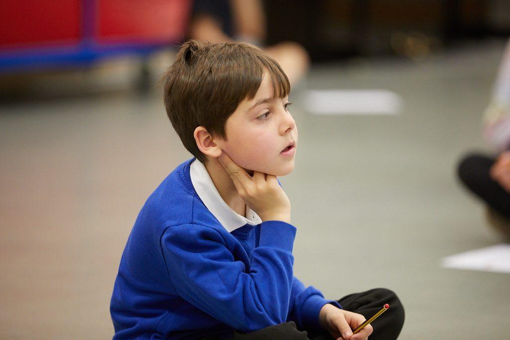 A boy in blue school uniform sits cross legged on the floor, taking his pulse.