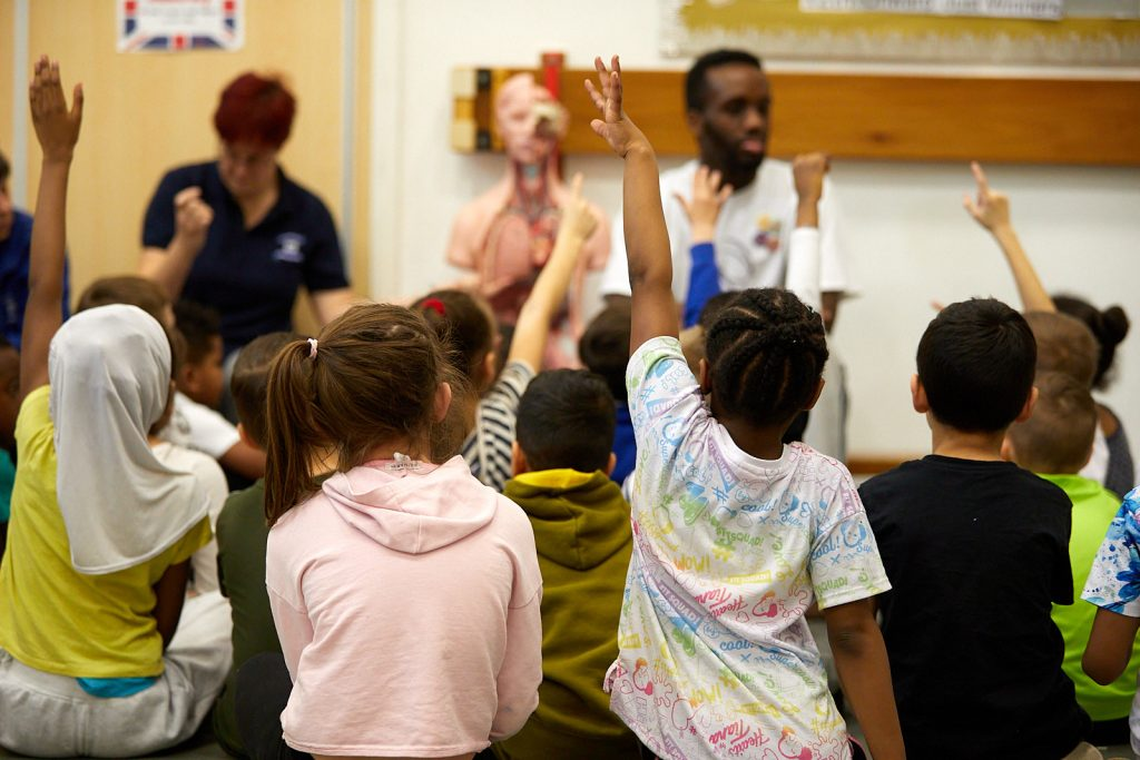 A group of school children with their hands raised are sat around a workshop leader who is pointing at a a human anatomy model.