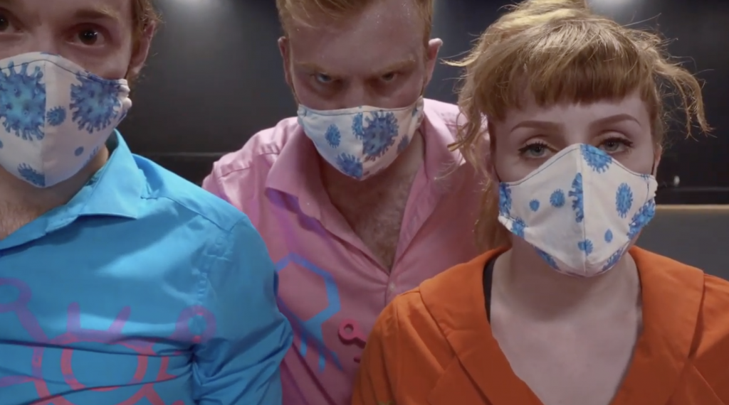 3 people wearing face masks and dressed in pink and blue clothing, looking intensely at the camera.