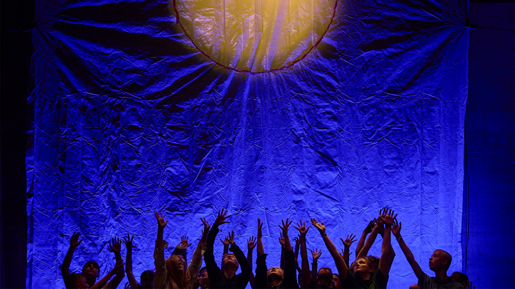 A dark stage, lit in blue, with a yellow sun in the background. A group of young people are standing in a group and reaching their hands up to the sky.