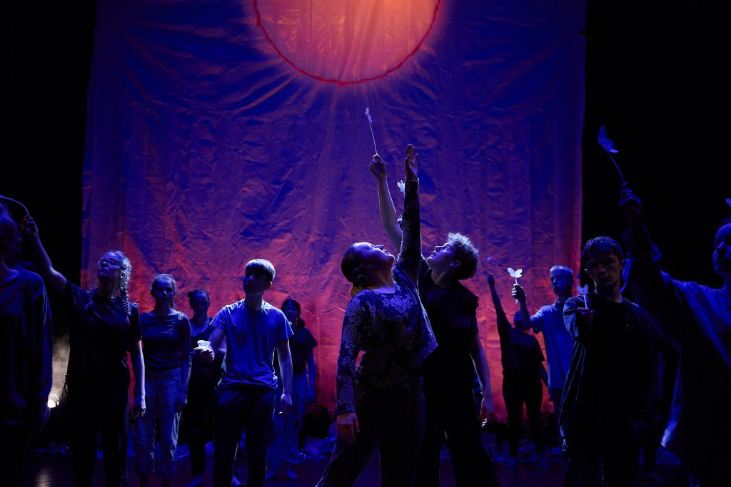 A dark stage, with a blue-lit backdrop and an image of the sun. On stage are 2 young people reaching their arms up towards the sun.