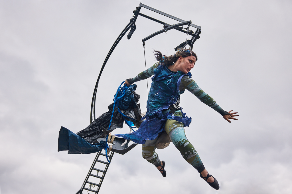 A woman in a dark blue tattered dress flies in the air, suspended from an aerial rig. She looks troubled and is holding a string of rubbish and paste waste.